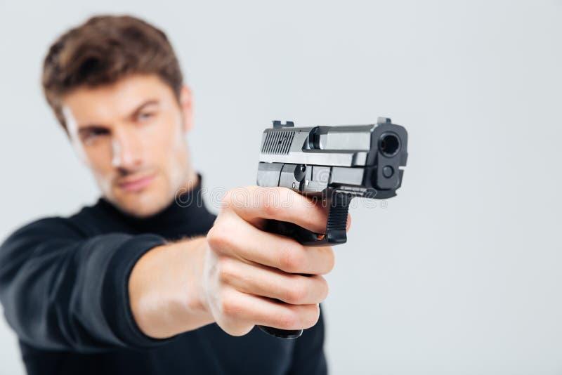 Nahaufnahme des fokussierten jungen Mannes, der mit Gewehr steht und zielt stockbilder