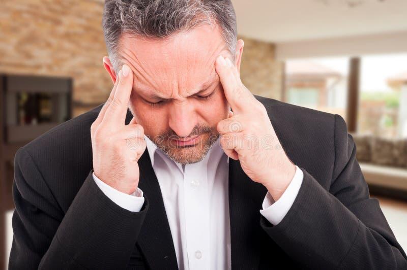 Nahaufnahme des frustrierten Grundstücksmaklers leiden unter Kopfschmerzen lizenzfreie stockbilder