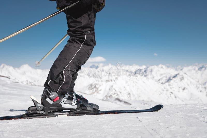 Nahaufnahme des Fu?es des Skifahrers des Athleten in den Skischuhen steigt in die Skis vor dem hintergrund Schnee-mit einer Kappe lizenzfreies stockfoto