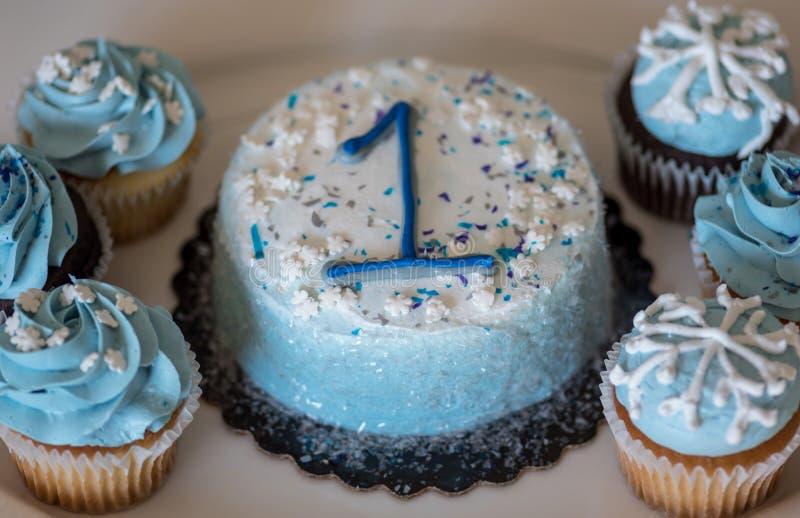 Nahaufnahme des Geburtstagskuchens mit Nummer Eins und kleinen Kuchen stockbild