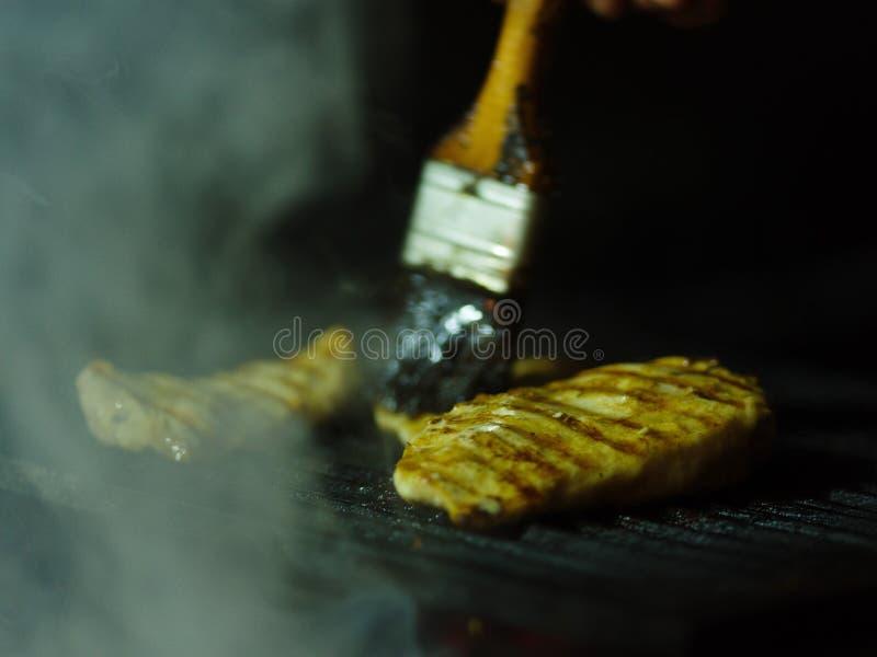 Nahaufnahme des gegrillten Huhns auf B-B-Q Gebratenes Fleisch und eine Ölbürste auf einem schwarzen Gitterhintergrund Kopieren Si lizenzfreie stockfotografie