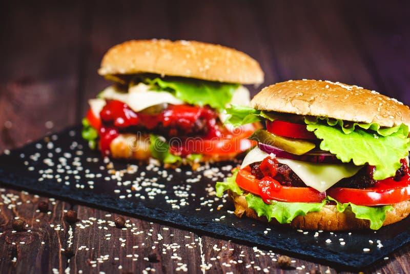 Nahaufnahme des gemachten Rindfleischhauptburgers mit Kopfsalat und Kartoffel diente auf Steinschneidebrett Dunkler h?lzerner Hin lizenzfreies stockbild