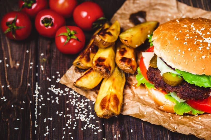 Nahaufnahme des gemachten Rindfleischhauptburgers mit Kopfsalat und Kartoffel diente auf Steinschneidebrett H?lzerner Hintergrund stockfotografie