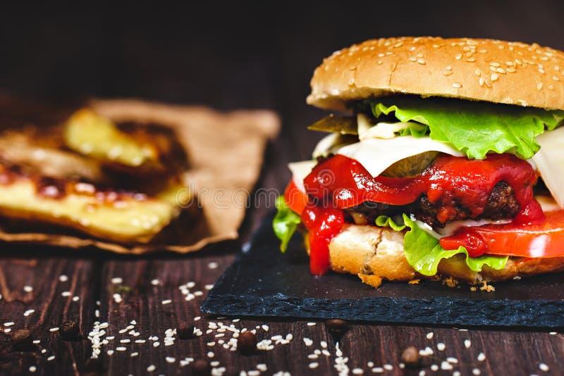 Nahaufnahme des gemachten Rindfleischhauptburgers mit Kopfsalat und Kartoffel diente auf Steinschneidebrett H?lzerner Hintergrund lizenzfreies stockfoto
