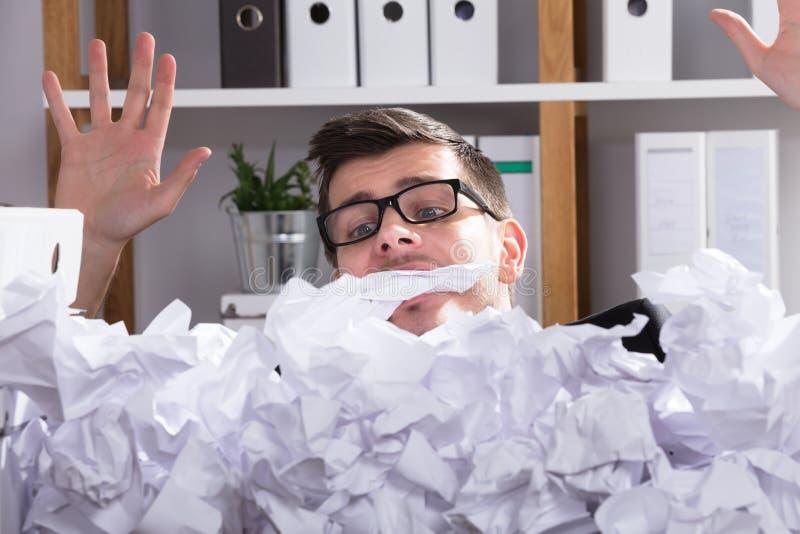 Nahaufnahme des Geschäftsmann-Behind Heap Of zerknitterten Papiers lizenzfreie stockbilder