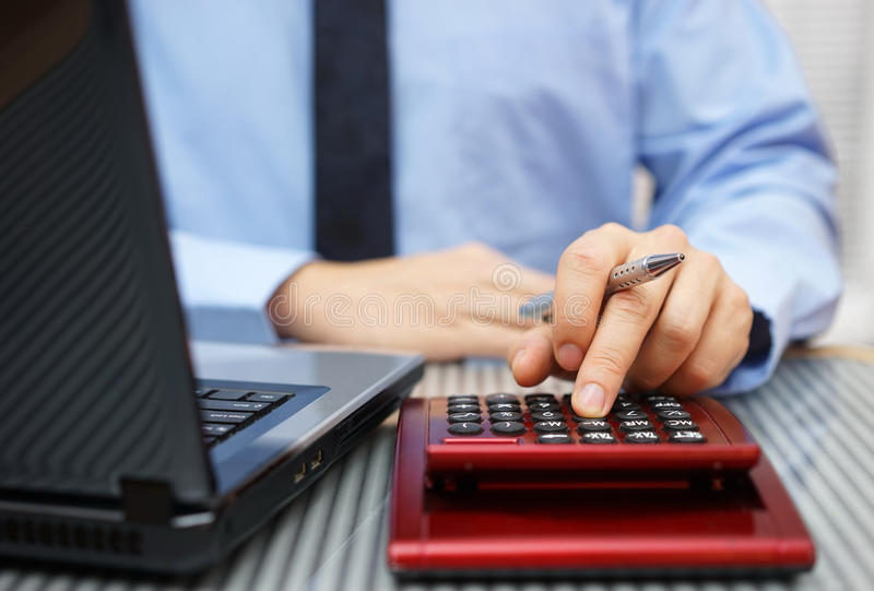 Nahaufnahme des Geschäftsmannes arbeitend an Taschenrechner und Laptop stockbild