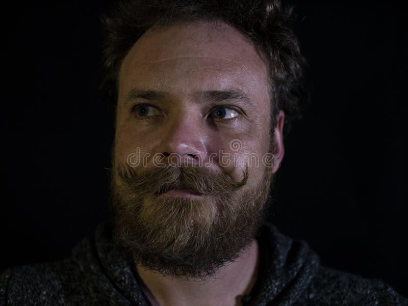 Nahaufnahme des Gesichtes eines Mannes mit einem Schnurrbart und des Bartes auf einem schwarzen backgrounde und einem Bart lizenzfreie stockfotos