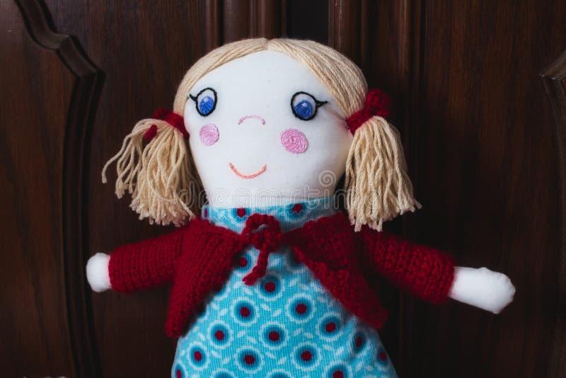Nahaufnahme des gestrickten angefüllten weichen Spielzeugs der Flickenpuppe für ein Kind lizenzfreie stockfotografie