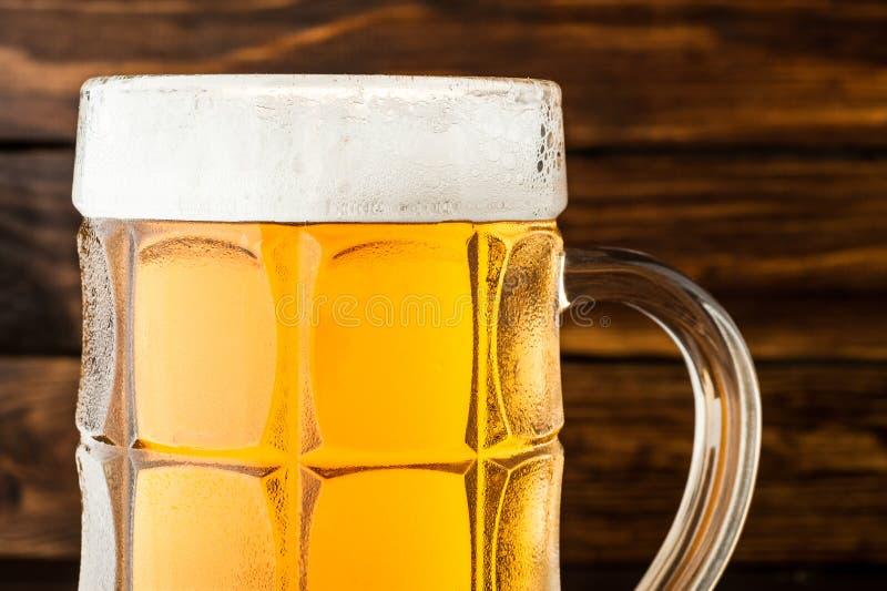 Nahaufnahme des Glases kalten schaumigen Lager-Bieres auf altem hölzernem backgro lizenzfreie stockfotos