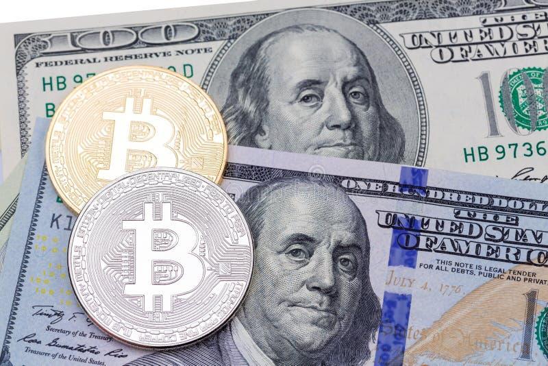 Nahaufnahme des goldenen und silbernen bitcoin auf hundert Dollar banknot stockbilder