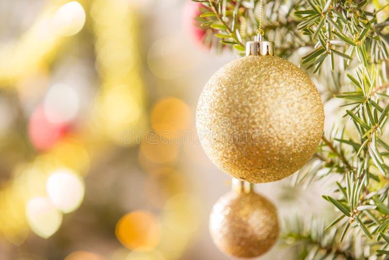 Nahaufnahme des Goldweihnachtsballs, der am Weihnachtsbaum hängt lizenzfreies stockfoto