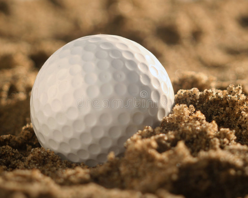 Nahaufnahme des Golfballes im Sand lizenzfreie stockfotografie