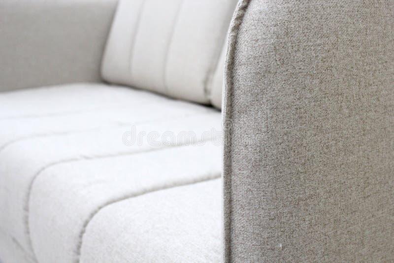 Nahaufnahme des grauen Sofas mit Armlehne Geweben, moderner Entwurf der neuen Möbel mit freiem Raum f?r Text stockbild