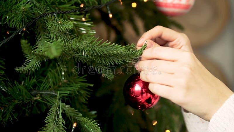 Nahaufnahme des hängenden Spielzeugs die Hand der Frau Weihnachts Verzierung des Weihnachtsbaums Neues Jahr und Weihnachtsfeierta lizenzfreie stockfotografie
