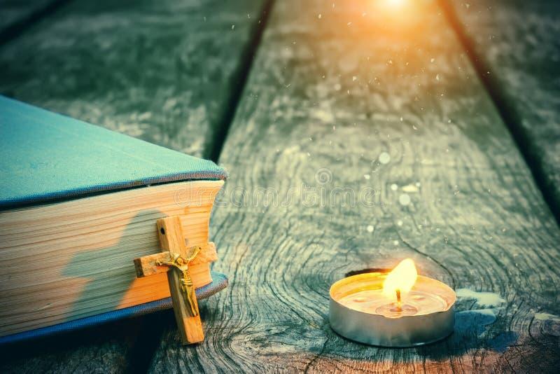 Nahaufnahme des hölzernen christlichen Kreuzes auf Bibel, brennende Kerze auf der alten Tabelle lizenzfreie stockfotografie