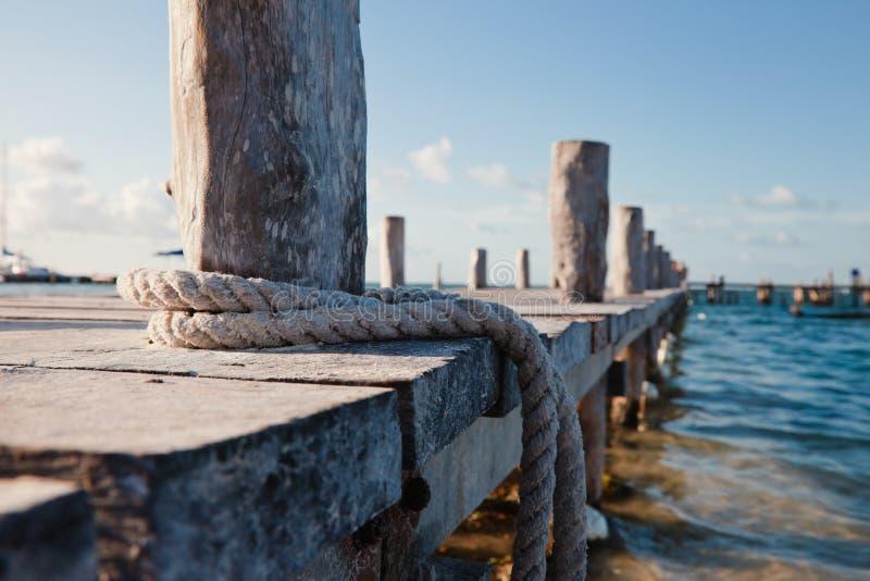 Nahaufnahme des hölzernen Piers, blaues Wasser, Bootsseil stockbild