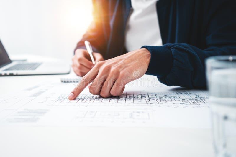 Nahaufnahme des Handarchitekten-Gebrauchslaptops und des errichtenden Planes auf Funktionstabelle in den Büroräumen lizenzfreies stockfoto