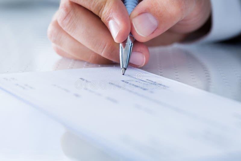 Nahaufnahme des Handfüllenden Schecks lizenzfreies stockbild