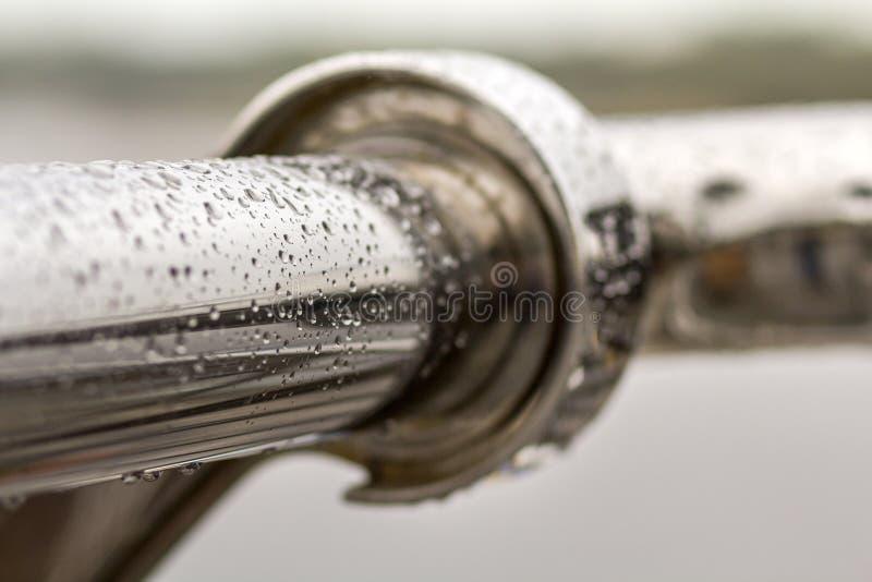 Nahaufnahme des horizontales Metallnass glänzenden Rohres mit großen Regenwassertropfen auf unscharfem abstraktem Hintergrund lizenzfreies stockfoto