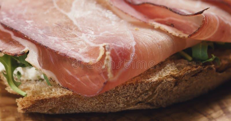 Nahaufnahme des italienischen Sandwiches mit Fleck, Arugulasalat und Bier stockbilder