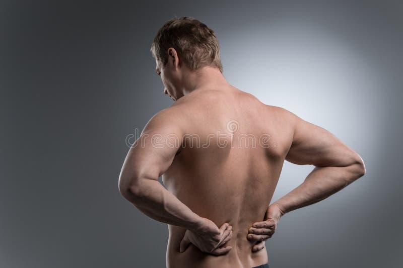 Nahaufnahme des jungen hemdlosen Mannes mit Rückenschmerzen lizenzfreie stockfotos