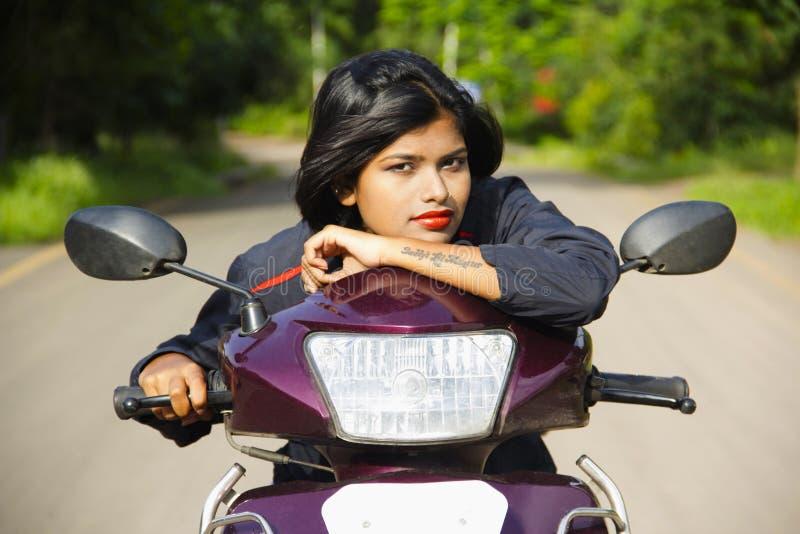 Nahaufnahme des jungen indischen Mädchens, das auf Fahrzeug- mit zwei Rädernrollergriff stillsteht und für Kamera, Pune aufwir stockbilder