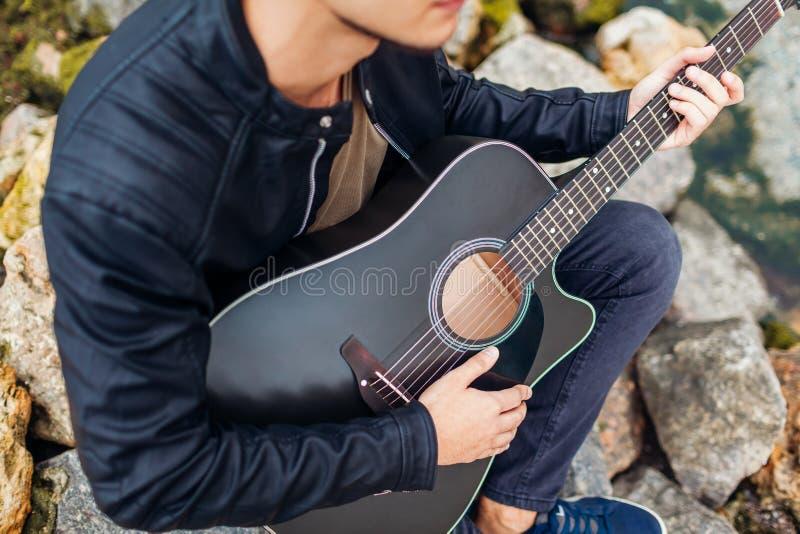 Nahaufnahme des jungen Mannes Akustikgitarre auf dem Strand spielend umgeben mit Rock am regnerischen Tag stockfoto