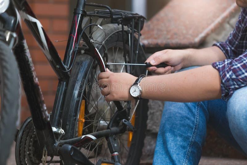 Nahaufnahme des jungen Mannes Fahrradhinterrad reparierend lizenzfreies stockbild