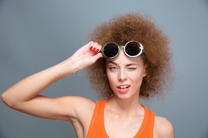 Nahaufnahme des jungen schönen blinzelnden Modells in der grünen Sonnenbrille stockfoto