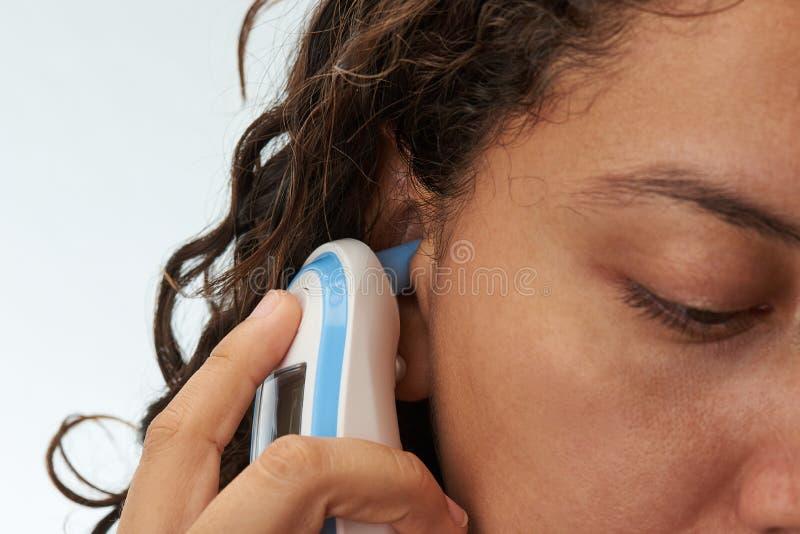 Nahaufnahme des Körperthermometers im Ohr lizenzfreie stockfotografie