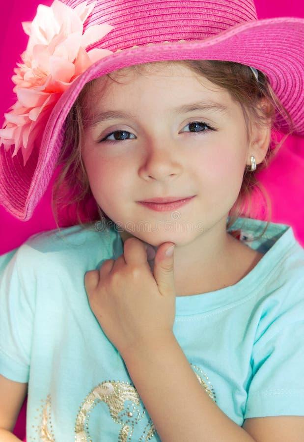 Nahaufnahme des kleinen Mädchens im rosa Sommerhut Schönes lächelndes Gesicht stockfotografie