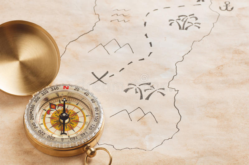 Nahaufnahme des Kompassses über beflecktem gelb gefärbtem Papierblatt mit Teil der Hand gezeichneten Schatzkarte lizenzfreie stockfotografie