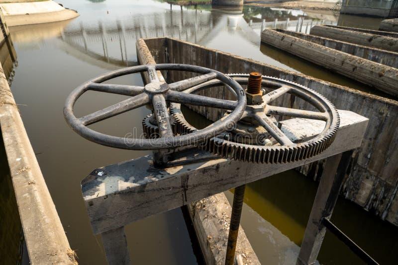 Nahaufnahme des Kontrolleschleusentors des schwarzen Metallzahnrads mit Texten in der thail?ndische Sprachbedeutung ?das Eigentum lizenzfreies stockfoto