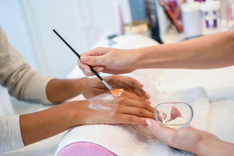 Nahaufnahme des Kosmetikers Creme auf Frau ` s Hand unter Verwendung des brus auftragend stockfotografie