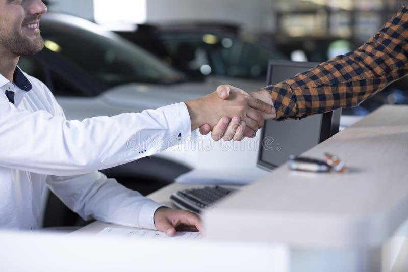 Nahaufnahme des lächelnden Autoverkäufers, der Käufer ` s Hand nach transa rüttelt stockfoto