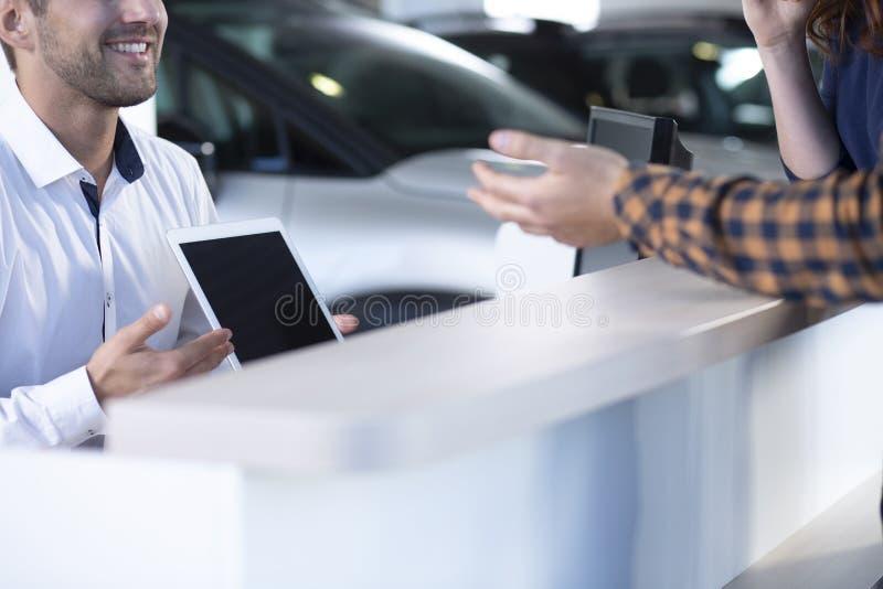 Nahaufnahme des lächelnden Berufsautoverkäufers mit dem Tabletten-Angebot stockbilder