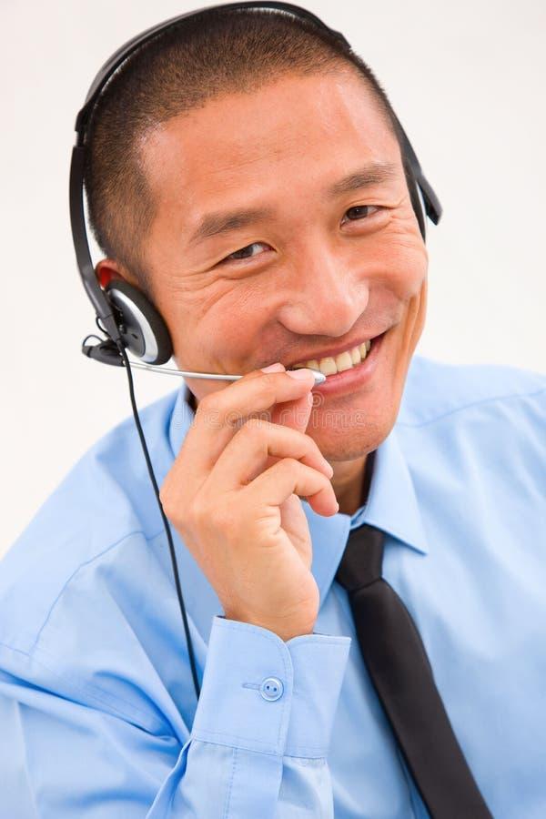 Nahaufnahme des lächelnden männlichen Kundendienstmitarbeitertragens stockfotos