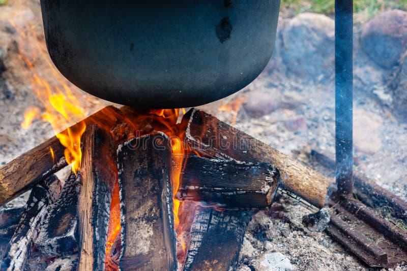 Nahaufnahme des Lebensmitteltopfes hängt über brennendem Feuer lizenzfreies stockbild