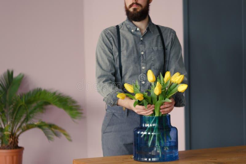 Nahaufnahme des leidenschaftlichen Gärtners um gelben Blumen herein kümmernd stockfotos