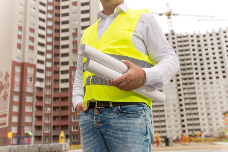 Nahaufnahme des männlichen Ingenieurs Pläne und Dokumente verwahrend lizenzfreies stockbild