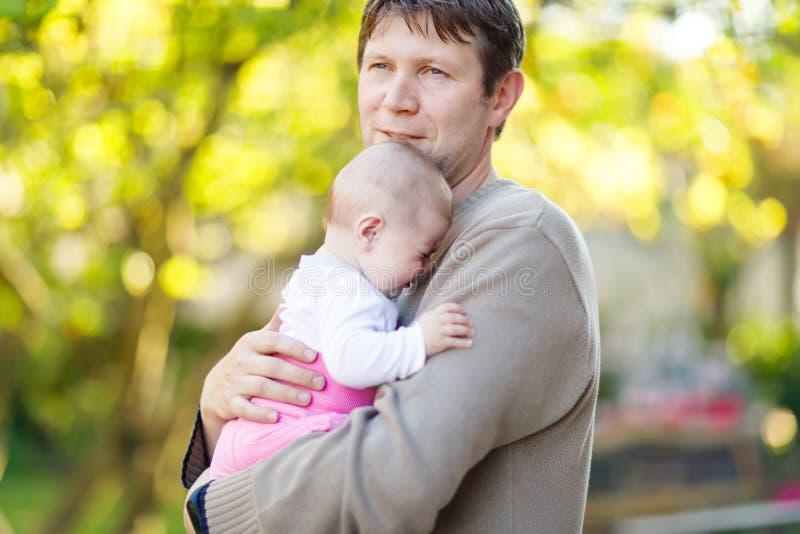 Nahaufnahme des müden jungen Vaters mit schreiendem Baby Vati mit Tochter draußen, Liebe Kleines Kinderschreien masseverbinder lizenzfreie stockfotos