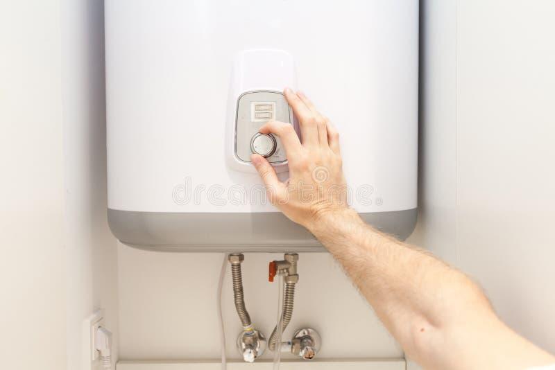 Nahaufnahme des Mannes übergibt die Einstellung der Temperatur des Wassers im elektrischen Kessel stockfoto