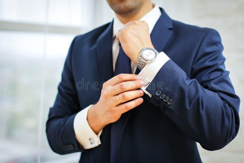Nahaufnahme des Mannes in der Klage mit Uhr auf seiner Hand, die seinen Manschettenknopf repariert Bräutigamfliegenmanschettenknö stockbild