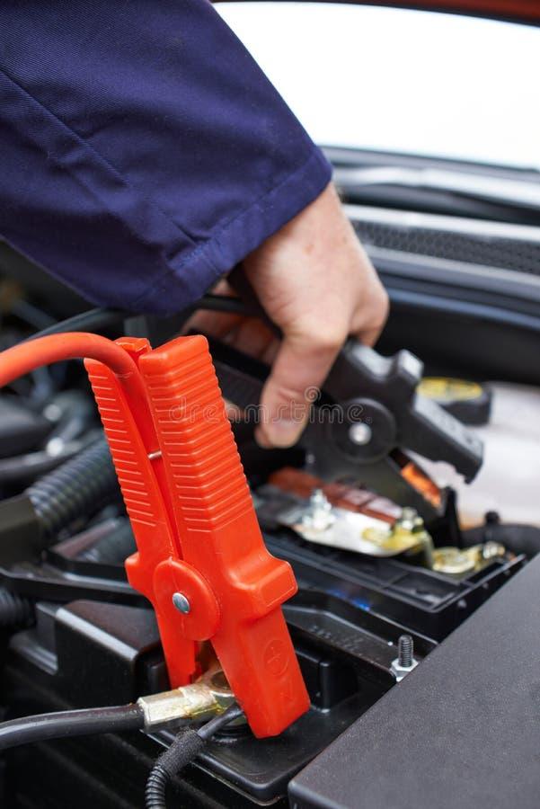 Nahaufnahme des Mechanikers Attaching Jumper Cables To Car Battery lizenzfreies stockfoto