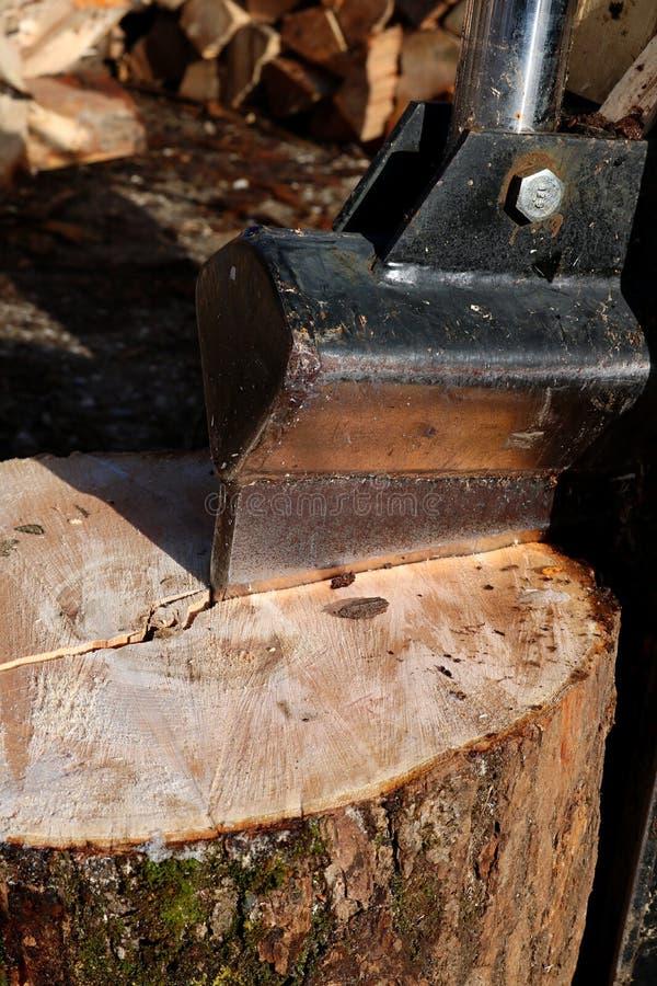 Nahaufnahme des Messers des vertikalen Klotzteilers, der in einen Holzklotz schneidet lizenzfreie stockbilder