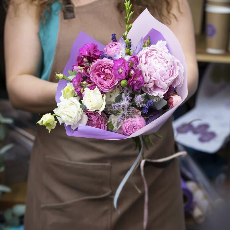 Nahaufnahme des modernen modernen Blumenstraußes der verschiedenen Blumen in den Händen des unerkennbaren Floristen des jungen Mä lizenzfreie stockfotografie
