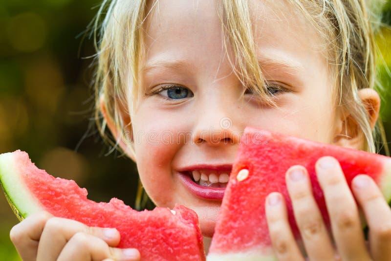 Nahaufnahme des netten glücklichen Kindes, das Wassermelone isst stockfotos