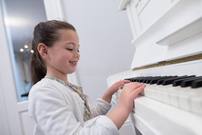 Nahaufnahme des netten Mädchens Klavier spielend lizenzfreies stockfoto