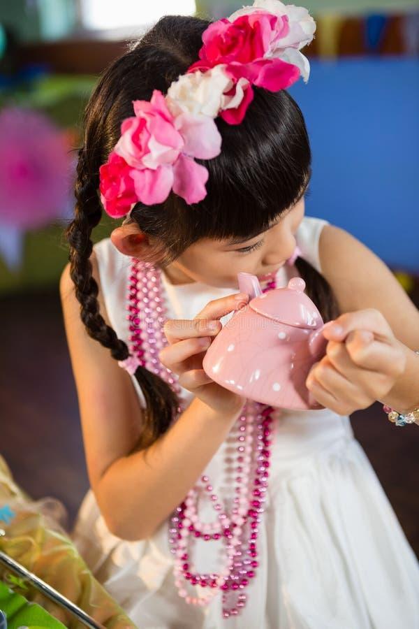 Nahaufnahme des netten Mädchens Spielzeugteekanne während der Geburtstagsfeier halten lizenzfreie stockfotos