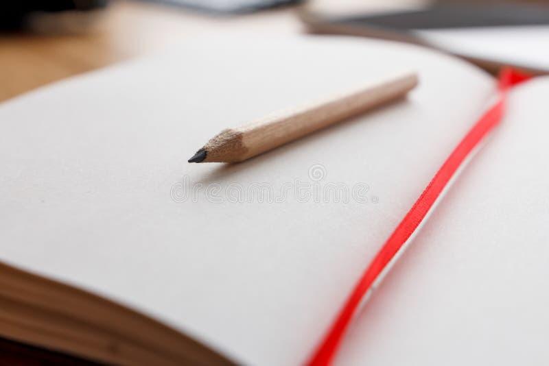 Nahaufnahme des offenen Notizbuches und des Bleistifts, rotes Bookmark stockfotografie